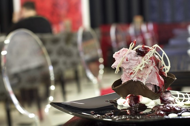 Strwberry ice cream with chocolate and strawberry syrup decoration served on table