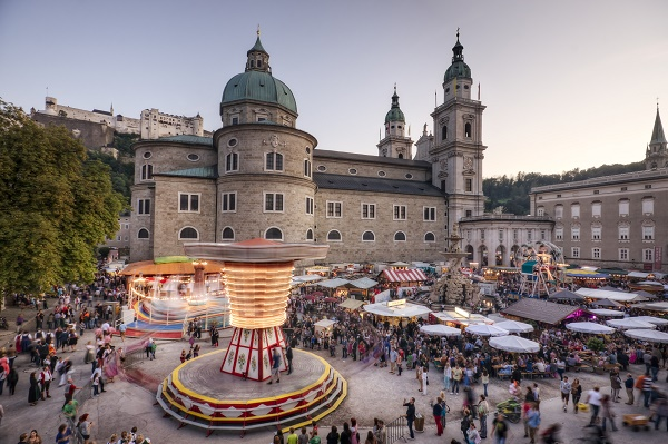 "Salzburg, Austria - September 24, 2011: Carnival swinging spinning around after sunset at the annual Rupertikirtag festival on Residenzplatz. This festival takes place each September to celebrate Salzburg's patron Saint Rupert as well as the sanctification of the city's main cathedral, seen here. The ""Kettenkarussell"" swing in this image has been in operation since 1848."
