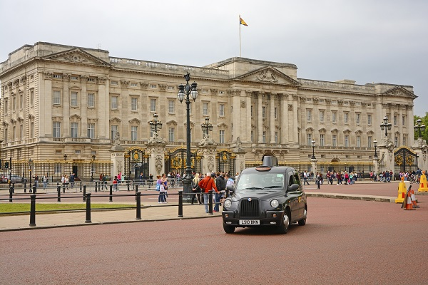 London, United Kingdom - July 14th, 2015: Buckingham Palace viewed from the Spur Road, with a black cab in theforeground. Many people walking on the square. The royal flag on the mast. Horizontal image in a cloudy day.